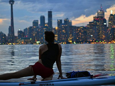 Gabby watches the city lights turn on during SUP Yoga