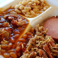 "Two-side dinner plate: Pulled pork, white beans, ""hillbilly beans"", and a slice of smoked bologn"