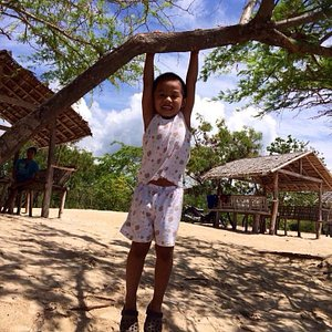 My nephew playfully swings by the tree in front of our cottage.