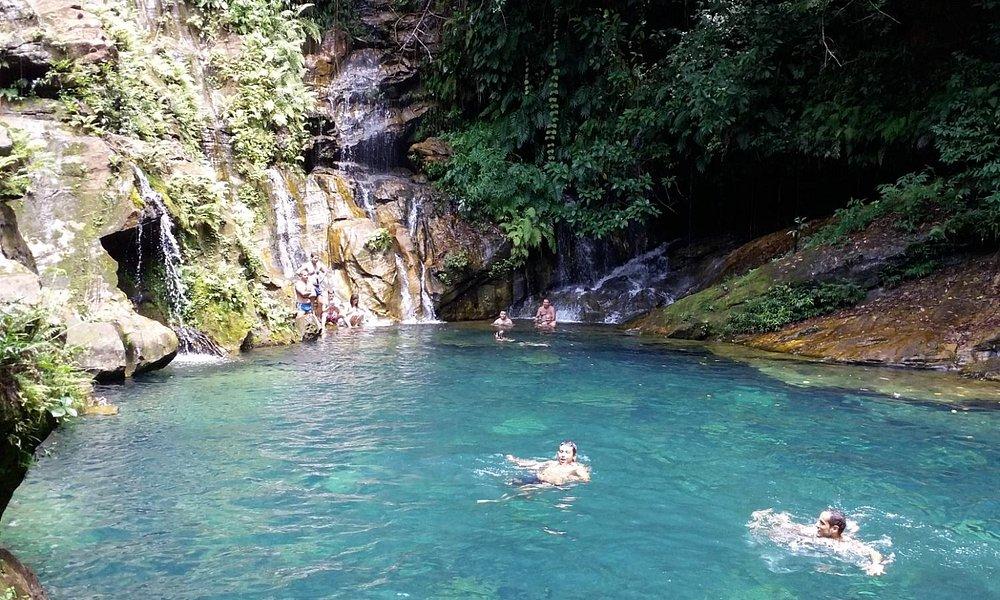 O poço azul, com pequenas caídas de água pela rochas.