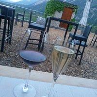 Un verre d'Humagne avec un Muscat en bulles sur un fond de vignes sierroises.