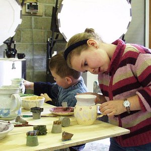 Here we have a couple of kids having a great time painting their own pots.