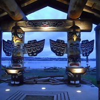 The rest centre across the street at dusk with uplit totems
