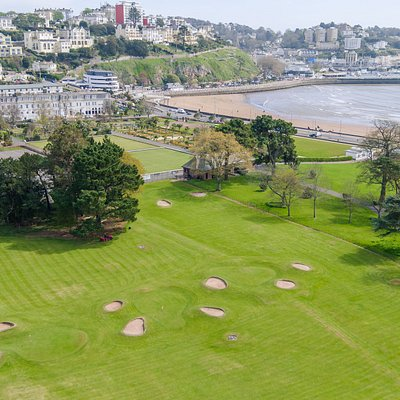 Ariel view of the golf course with the sea and beach in the background.