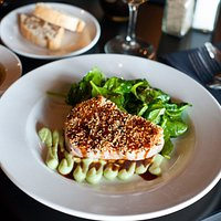 Sesame encrusted tuna on a bed of wasabi aioli and topped with soy glaze
