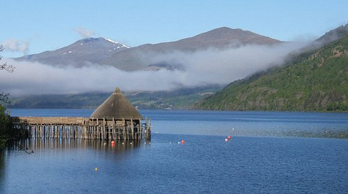 The Crannog against the beautiful Highland scenery of Loch Tay and the hills