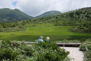 湿原展望台、ベンチがあり休憩できる。奥に見えるは井戸岳、大岳。