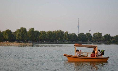 Vista de barco com família passeando no lago com a Torre de TV de Luoyang ao fundo.