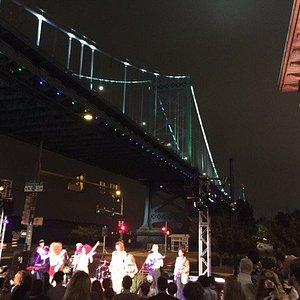Outdoor music performance at Fringe Arts; Ben Franklin Bridge lit up
