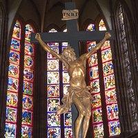 Kreuz mit Kirchenfenstern im Hintergrund