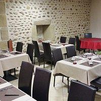 salle de restaurant avec un super mur en galet, des fauteuils confortables