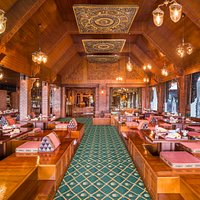 Dine at charming floor seating and low tables beneath with large, handsomely dressed windows.