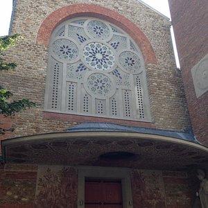 Entrée, peintures murales de chaque côté, grand vitrail au-dessus