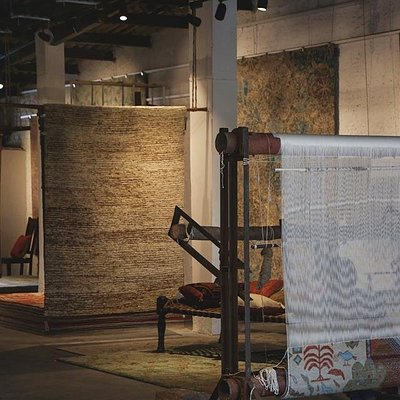 Surrounded by globally renowned designer rugs, our artisan gracefully weaves his interpretation
