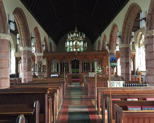 Historic church with restored Devon rood screen, carved baptismal font. Cemetery monument Bertra