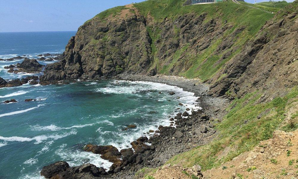 岬の突端から灯台と風の館を振り返る