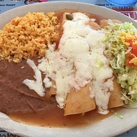 One photo shows some chicken enchiladas topped with cheese, also retried beans, rice and lettuce
