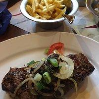 Steak mit Knoblauch, Zwiebeln, Pommes und Salat
