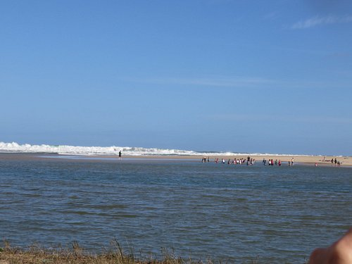 The open sea viewed from the island with children playing on the lagoon beach with waves breakin