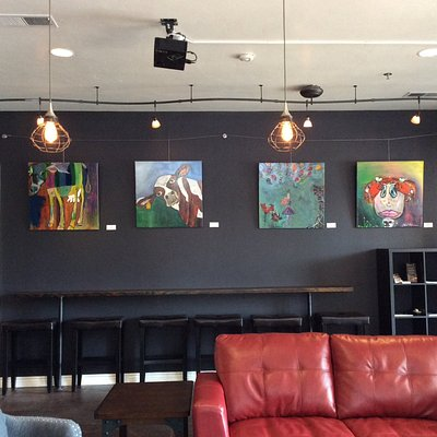 Display wall of local artist, big red couches for you to relax after your travels
