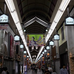 Overhead store signs brightly lit up along the way under the roof