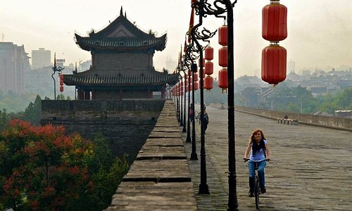 My wife riding a bike on the wall of Xi'an