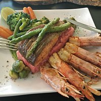 Seared salmon with locally caught prawns on beetroot and potato mash with sprouts and asparagus.