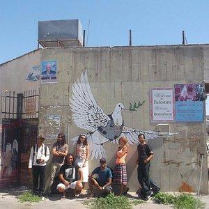 A group photo in front of Banksy original graffiti artwork - Bethlehem