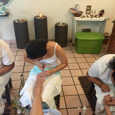 Hard working ladies doing pedicures.