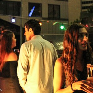 Attendees enjoying the Hills' beautiful rooftop bar, the second stop on their bar crawl!