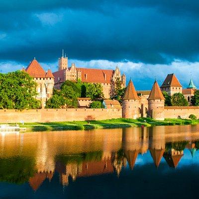 Замок Мариенбург - один из самых больших в мире кирпичных замков и его отражение в протоке Ногат