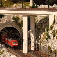A train exitinga tunnel, passing under a bridge