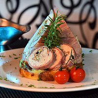 Chicken Roulade set on baked pressed potatoes served with berry Jus.