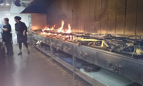 Panorámica cocina con zona parrilla con algún Arroces al fuego