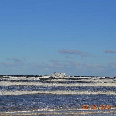 widok z plaży na przepływający statek