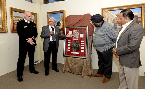 Dr Parekh (owner of the collection) describing a newly unveiled multi-faith shield