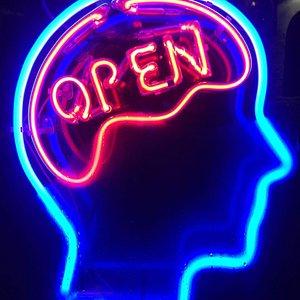 Openmind. Neón de la ventana que anuncia cómo es el lugar.