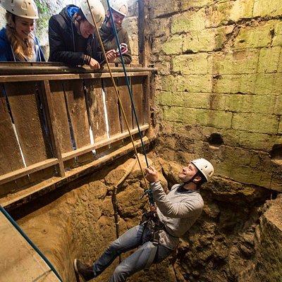 Abseilen in een oude waterput. Je komt uit in het ondergrondse labyrint.