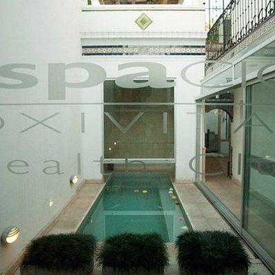 la piscina in/ out  con  bancas dentro y jacuzzi , climatizada en la época invernal