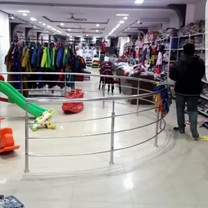 A inside view of vastra vinod with a lot of stock for men women and children. And playing facili