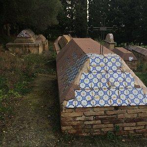 Iron cross on ceramic tiled grave