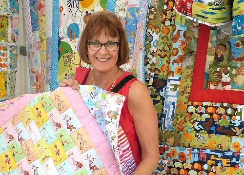 Scrappy Bags stall showing off the quilt she was working on.