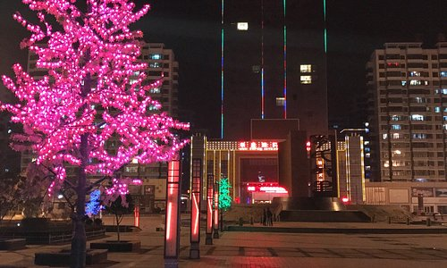 Outside the hotel at night and also features a sculpture highlighting the Li family name.