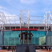 Old Trafford featuring the Trinity statue outside of the East Stand