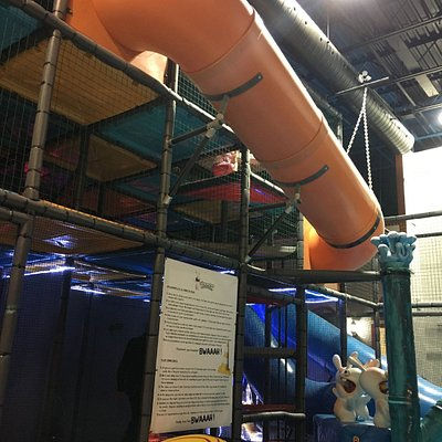 jungle gym with 2 slides that drop into small ball pit, larger ball pit in same room.
