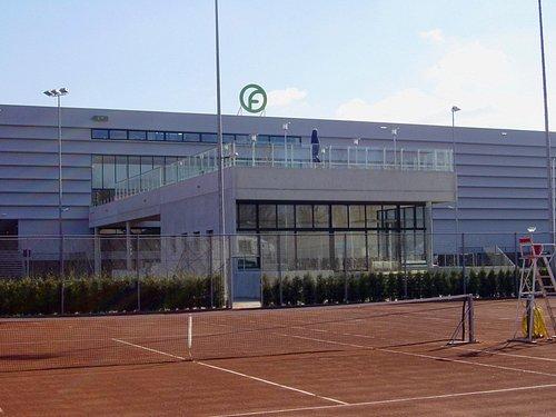 het gebouw met op de eerste verdieping het dakterras gezien vanaf de buiten tennisbanen