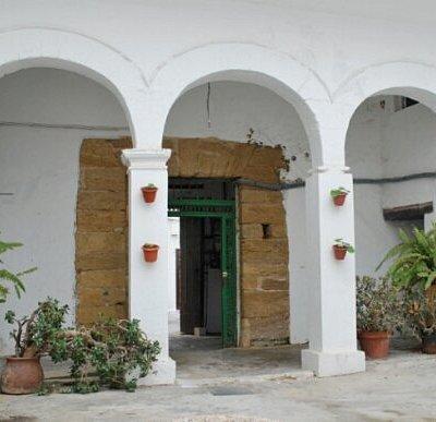 Arcos blancos y entrada de piedra en el patio de Eolo