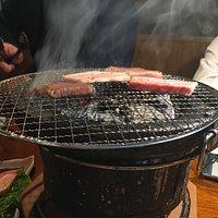 うちこ豚を炭火で焼いてます