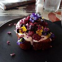Banana bread with fresh berries and yogurt - topped with edible flowers