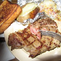 Texas toast, loaded baked potatoes (2), and Ribeye Steak, very rare